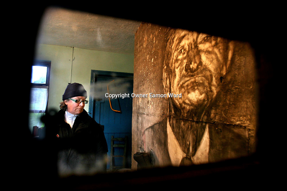 Artist Dierdre Mahony with a Soot drawing of Postmaster Mattie on the Chimney Breast of the old Post Office at Kilnaboy,Co Clare...Photograph by Eamon Ward