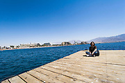 A woman on the pier, Eilat, overlooking the city of Eilat, pop. 55,000, is Israel's southernmost city in the Southern District of Israel. Adjacent to the Egyptian city of Taba and Jordanian port city of Aqaba, Eilat is located at the northern tip of the Gulf of Aqaba, which is the eastern sleeve of the Red Sea.