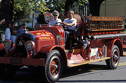 Americana antique fire engine leads march in small town holiday celebration parade.