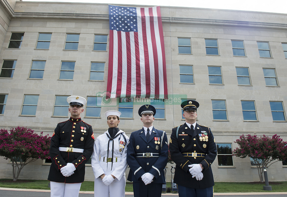 September 11, 2016 - Arlington, VA, United States of America - U.S Service members stand in front of a flag hanging from the Pentagon where the aircraft plowed into the building 15-years-ago during a remembrance ceremony commemorating the 15th anniversary of the 9/11 terrorist attacks at the Pentagon September 11, 2016 in Arlington, Virginia. (Credit Image: © Tsgt. Brigitte N. Brantley/Planet Pix via ZUMA Wire)