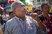 "15 JANUARY 2014 - BANGKOK, THAILAND: SUTHEP THAUGSUBAN, former Deputy Prime Minister of Thailand and leader of the Shutdown Bangkok anti-government protests, walks up Sukhumvit Road in Bangkok during a protest march. Tens of thousands of Thai anti-government protestors continued to block the streets of Bangkok Wednesday to shut down the Thai capitol. The protest, ""Shutdown Bangkok,"" is expected to last at least a week. Shutdown Bangkok is organized by People's Democratic Reform Committee (PRDC). It's a continuation of protests that started in early November. There have been shootings almost every night at different protests sites around Bangkok. The malls in Bangkok are still open but many other businesses are closed and mass transit is swamped with both protestors and people who had to use mass transit because the roads were blocked.    PHOTO BY JACK KURTZ"