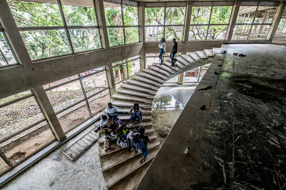 People sit on the stairs of the abandoned Ducor Hotel, once the most prominent hotels in Monrovia, Liberia