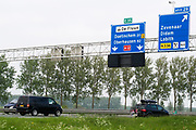 Bij Zevenaar rijdt verkeer over de A12 richting Duitsland. Boven de borden zijn camera's aangebracht voor trajectcontrole.<br /> <br /> Near Zevenaar traffic on the A12 towards Germany. Above the signs are cameras put for speed checking over a longer distance.