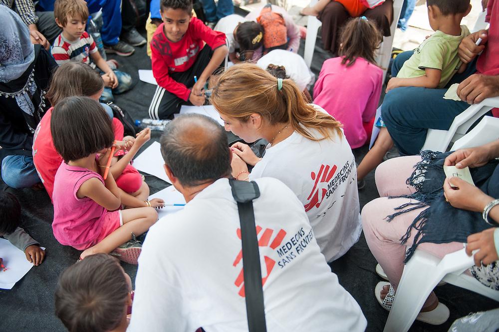 Lena Zachou the MSF psychologist together with the Afghan translator Bashir doing a programme for refugee children at the port of Mytiline.