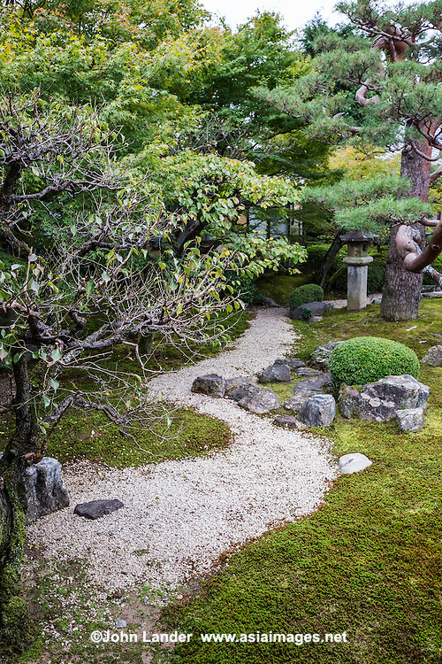 """Myokenji Kohrin Kyokusai Garden pays homage to Ogata Kohrin, who was a renowned painter from the Edo Period.  This garden's design follows a pattern based on 'Sho Chiku Bai Zu"""" a scroll painting by Kohrin.  Centered around the pine tree is a white sand - the composition expresses a curving water stream."""