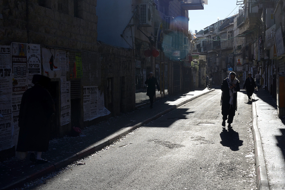 An Utra-Orthodox Jewish man is passing in the street  during celebrations of Purim Holiday in the Ultra-Orthodox Jewish neighbourhood of Mea Shearim in Jerusalem, on March 6, 2015. The Jewish holiday of Purim commemorates the salvation of the Jews living with in the borders of the ancient Persian Empire. Purim customs include food gifts, charity, wearing costumes and drinking heavily.
