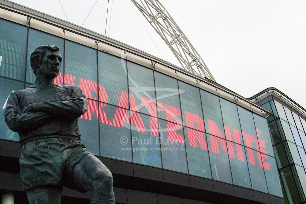 Wembley Stadium, London, November 17th 2015. Hours befor kick-off French and England fans begin to gather outside Wembley Stadium as both England and France national teams are poised to play in an emotional tie just days after the tragic death of 130 people in the Paris Islamist attacks. PICTURED:  Brotherhood. Sir Bobby Moore's statue watches over Wembley. // Licencing Contact: paul@pauldaveycreative.co.uk Mobile 07966 016 296