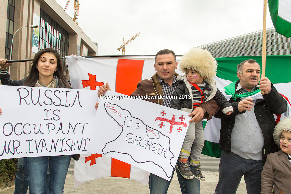 Brussels 20130419 A small group of people from Georgia demonstrate in front of the European Commission. They state to be for Europa and against influence of Russia. Small boys wear the traditional Georgian fur hats called Chokha,part of their proud cultural heritage.A girl holds poster with text: Russia is occupant mr ivanishvi and a plan of the country