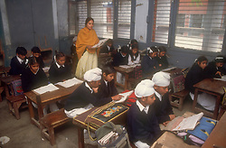 School girls and boys sitting at desks reading books with female teacher supervising in senior secondary modern school; Punjabi University; Patiala; Punjab; India,