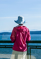 A woman wearing a hat and windbreaker standing at the railing outside on a Washington State ferry in the San JUan Islands enjoying the views, Washington, USA.