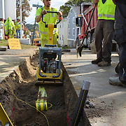 """BATH, Maine -- 10/8/14 -- Tyler Rowe of Enterprise Trenchless Technology Incorporated closes up a gas line trench across Washington St. in Bath on Wednesday with a weight compactor. Gas lines began going in on Aug 20. Washington St -- from Centre to Bowery St -- is complete and the company is now working their way down the side streets. In the foreground is the 2"""" gas line used to deliver natural gas to Bath homes. Equipment Operator Josh Worth said,<br /> """"The most difficult part of this job is working around the ledge. """" The minimum depth for a two inch pipe is 38 inches. """"There are a lot of places here in Bath where the ledge is closer to the surface than our minimum depth."""" Photo ©2014 by Roger S. Duncan."""