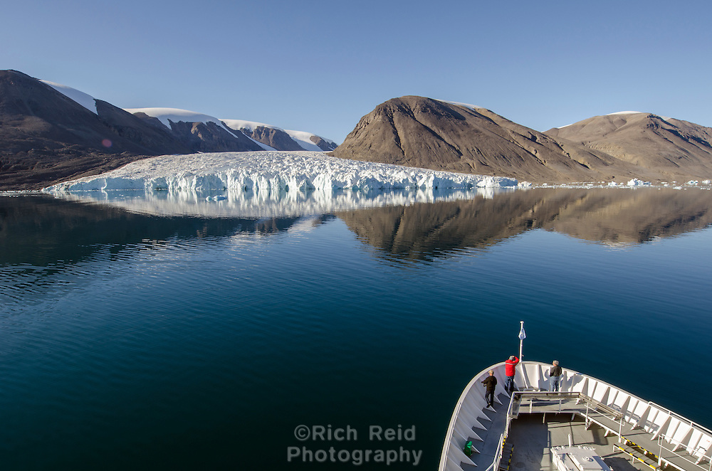 Bow of the National Geographic Explorer and tidewater glacier in South Cape Fiord on Ellesmere Island in Nunavut, Canada.