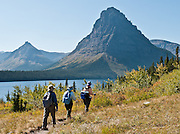 "Sinopah Mountain, hikers, and Two Medicine Lake, in Glacier National Park, Montana, USA. Since 1932, Canada and USA have shared Waterton-Glacier International Peace Park, which UNESCO declared a World Heritage Site (1995) containing two Biosphere Reserves (1976). Rocks in the park are primarily sedimentary layers deposited in shallow seas over 1.6 billion to 800 million years ago. During the tectonic formation of the Rocky Mountains 170 million years ago, the Lewis Overthrust displaced these old rocks over newer Cretaceous age rocks. Glaciers carved spectacular U-shaped valleys and pyramidal peaks as recently as the Last Glacial Maximum (the last ""Ice Age"" 25,000 to 13,000 years ago). Of the 150 glaciers existing in the mid 1800s, only 25 active glaciers remain in the park as of 2010, and all may disappear by 2020, say climate scientists."