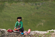 A lady is washing the cloth beside the lake in H'Mong Village, in Pho Cao, Ha Giang. Their life standard is so low, they are lack many thing, from pure water, soap... but it's so suprised that Omo, a famous detergent is appeared everywhere... in far and long hill area.