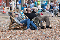 © Licensed to London News Pictures. 01/06/2014. Brighton, UK. A couple relaxes on the beach in the Sun. Despite a good start to the weekend on Saturday the weather has deterred some people from coming to the beach. Photo credit : Hugo Michiels/LNP