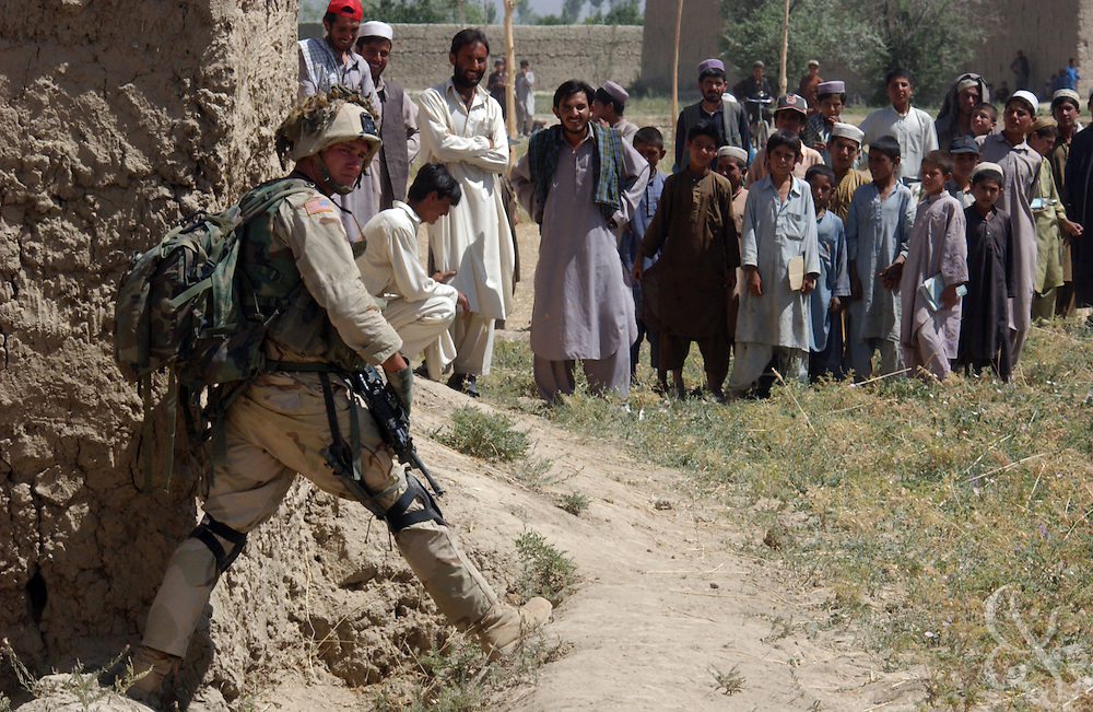 """Local Afghans watch as a U.S. Army soldier from the 101st Airborne blocks a footpath during """"sensitive site exploitation"""" mission or SSE July 16, 2002 in village of Hesarak, eastern Afghanistan. The army raided the village to conduct a follow-up search for possible Al-Qaida or Taliban intelligence materials and to provide humanitarian aid. The raid was a follow-up to a similar raid there four days ago that yielded two detainees and undisclosed intelligence materials."""