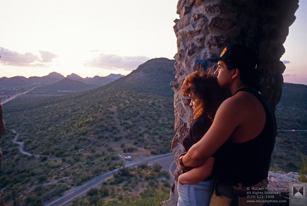 "Young couple watches sunset from ""A Mountain,"" Tucson Mtn. Park, Tucson, AZ.©1993 Edward McCain. All rights reserved. McCain Photography, McCain Creative.."
