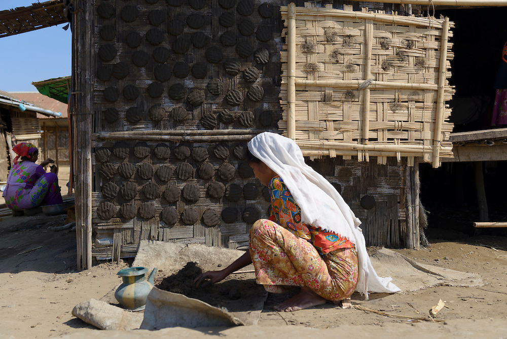 A woman uses cow dung to make alternative fuel at the Say Tha Ma Gyi Camp near Sittwe. 2015-02-05.