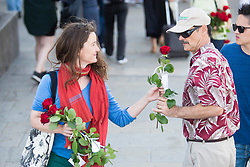 © Licensed to London News Pictures. 26/04/2016. London, UK.  Roses are handed out by members of the 1000RosesLondon group on London Bridge a week after a terror attack killed eight people. The group hopes to promote love and solidarity. Photo credit: Cliff Hide/LNP
