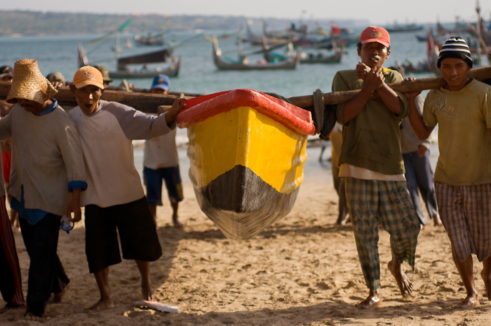 Fishermen carry their boats from the water's edge after a day of fishing.