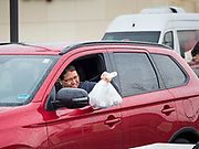 """11 APRIL 2020 - DES MOINES, IOWA: A motorist picks a ready to cook pasta meal during a food distribution in Des Moines. Most non-essential businesses in Iowa are closed until 30 April. Because of business closings causes by the Novel Coronavirus (SARS-CoV-2) pandemic, well over 100,000 Iowans filed first time claims for unemployment in the last three weeks, more than applied during the peak of the Great Recession of 2008. Local food banks have seen an unprecedented spike in people seeking nutritional assistance. Midwest Foods, a Des Moines based company and owner of Ginos Fine Italian Foods, gave away 1,000 complete dinners with sauce, noodles, salad, and dressing Saturday morning. People started lining up 3 hours before the food distribution began. The food distribution was done following """"social distancing"""" guidelines and all of the workers wore masks and gloves.     PHOTO BY JACK KURTZ"""