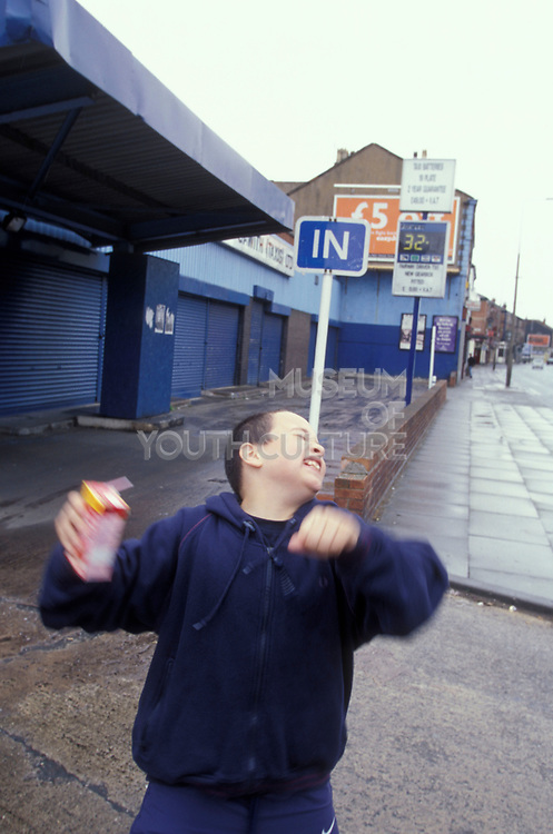 Laughing boy on the street holding a drink carton