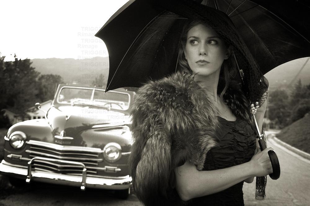 A model holding an umbrella standing near an old car