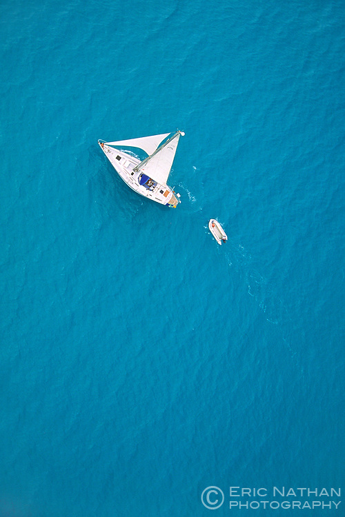 A yacht towing a dinghy sails in the Caribbean sea off the coast of Antigua. Photo taken from a helicopter.