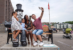 "© Licensed to London News Pictures.  01/07/2018; Bristol, UK. Gromit Unleashed 2. The Neal family with Autumn-Rose aged 6 and Aurelia aged 7 months (verbal permission given for photo) pose with the ""Wallambard"" Wallace character (after Isambard Kingdom Brunel) installed outside the SS Great Britain at Bristol Harbourside for the Gromit Unleashed 2 sculpture trail. Gromit Unleashed 2 which officially begins on 02 July will see the Academy Award®-winning character Gromit by Nick Park at Aardman Animations returning to Bristol in 2018 for the second time on sculpture trails to raise money for  the Grand Appeal charity. The character of Gromit will be joined by Wallace and their arch nemesis Feathers McGraw. The trail will feature over 60 giant sculptures designed by high-profile artists, designers, innovators and local talent. Sculptures will be positioned in high footfall and iconic locations around Bristol and the surrounding area. Photo credit: Simon Chapman/LNP"