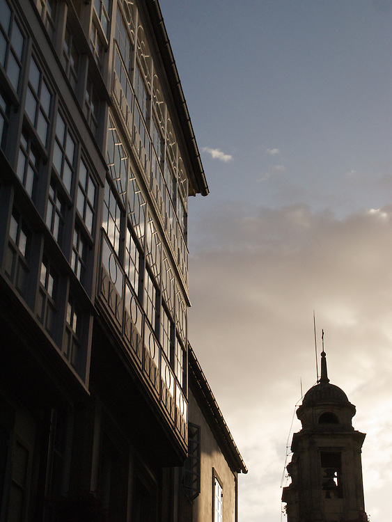 An old spire of a church contrasts with a more modern construction in Santiago de Compostela. the evening light brought out the silhouette and light on the buildings.