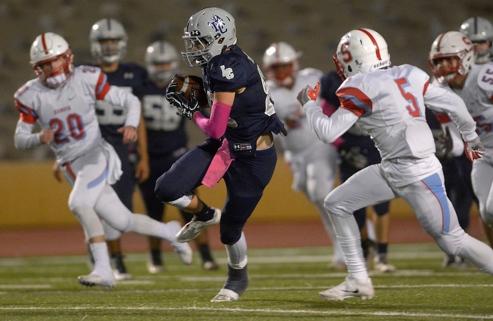 gbs102016j/SPORTS -- La Cueva's Tristan Roswold, center, catches a pass and runs between Sandia's Ryan Brown, 20 and  Izaiah Bernal, 5, during the game at Wilson Stadium on Thursday, October 20, 2016.(Greg Sorber/Albuquerque Journal)