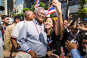 "21 JANUARY 2014 - BANGKOK, THAILAND:  A woman stops SUTHEP THAUGSUBAN for a ""selfie"" during a march down Thanon Naradhiwas Rajanagarindra in the financial district of Bangkok. Suthep, the leader of the anti-government protests and the People's Democratic Reform Committee (PDRC), the umbrella organization of the protests, led a march through the financial district of Bangkok Tuesday. Shutdown Bangkok has entered its second week with no resolution in sight. Suthep is still demanding the caretaker government of Prime Minister Yingluck Shinawatra resign and the PM says she won't resign and intends to go ahead with the election.    PHOTO BY JACK KURTZ"