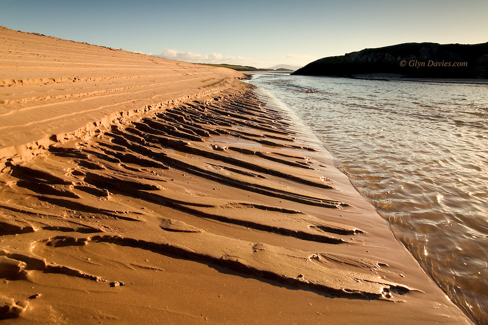 As the tide recedes  the water in the sand bank drains away carving temporary and unusual channels in the sand bank, at right angles to the direction of the river. The mountains of Eryri can be seen in the distance.