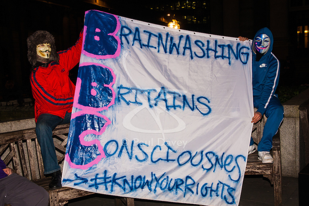 """London, December 23rd 2014. Online activism group Anonymous march through London from the City to the BBC's HQ on Great Portland Street in protest against alleged biases and coverups of a """"paedophile ring"""". PICTURED: Protesters made up their own versions of the BBC acronym."""