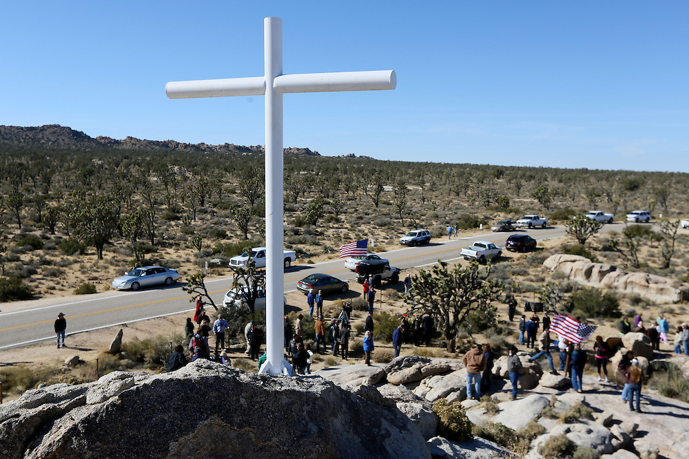 A cross overlooks a crowd during a dedication for the Mojave cross on Veterans Day in Cima, California on Sunday, November 11, 2012.  A battle has been brewing for over Thirteen years over whether the cross can legally stay on Sunrise Rock because it violates Separation of Church and State and is in the Mojave National Perserve which is on Federal Lands.  The Veterans of Foreign Wars and American Legion Society raised money to purchase the plot of land and has kept the cross in place and today serves as war memorial.(Photo by Sandy Huffaker)