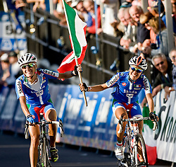 (Geelong, Australia---2 October 2010) Italian riders Luisa Tamanini (Left) and Elena Berlato (right) celebrate a job well done by riding over the finish line with their flag. Their teammate Giorgia Bronzini won the race with a last second charge. They were competing in the Elite Women's Road Race at the 2010 UCI World Championships.  [2010 Copyright Sean Burges / Mundo Sport Images -- www.mundosportimages.com]