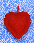 A red heart cushion hanging from a pushpin.