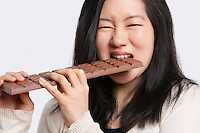 Portrait of a young woman eating a large chocolate bar over light gray background