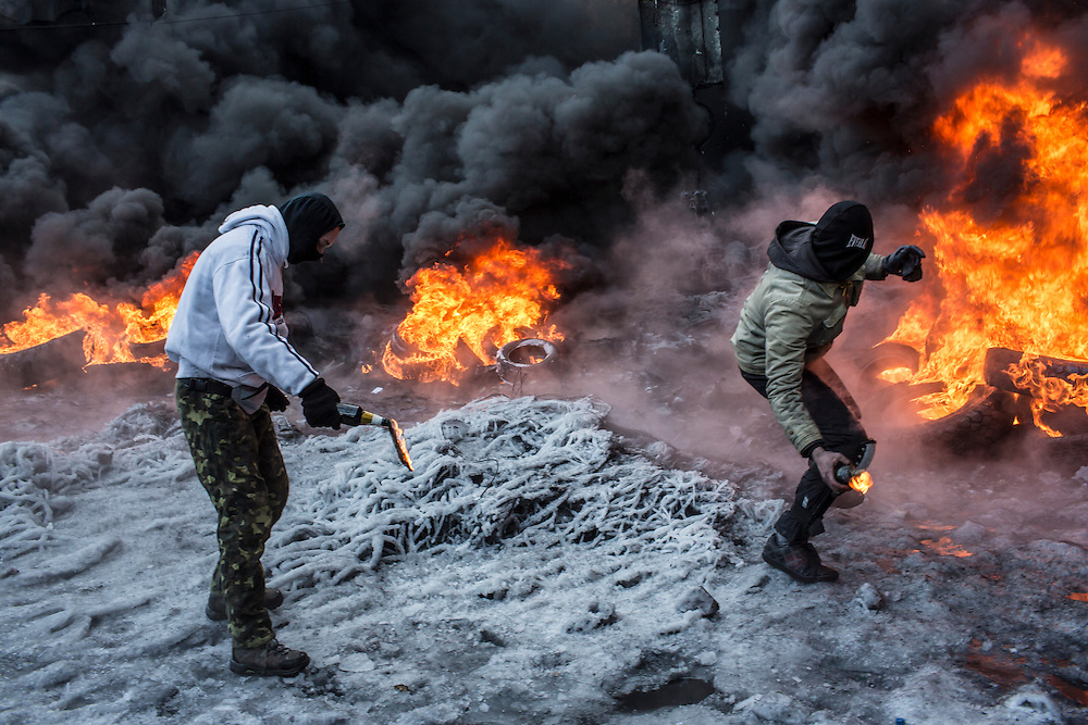 KIEV, UKRAINE - JANUARY 25: Anti-government protesters throw Molotov cocktails at police during clashes on Hrushevskoho Street near Dynamo stadium on January 25, 2014 in Kiev, Ukraine. After two months of primarily peaceful anti-government protests in the city center, new laws meant to end the protest movement have sparked violent clashes in recent days. (Photo by Brendan Hoffman/Getty Images)