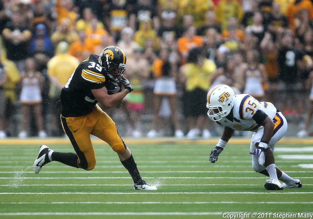 September 3, 2011: Iowa Hawkeyes tight end Brad Herman (39) protects the ball as Tennessee Tech Golden Eagles linebacker Justin Vann (35) prepares to hit him after a catch during the first half of the game between the Tennessee Tech Golden Eagles and the Iowa Hawkeyes at Kinnick Stadium in Iowa City, Iowa on Saturday, September 3, 2011. Iowa defeated Tennessee Tech 34-7 in a game stopped at one point due to lightning and rain.