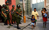 A woman breast feeds her child as she walks with her family past  various members of Gutemala's police and military as they preform a early morning raid on the notoriously violent area of the, Barrio El Gallito  Friday May 16, 2008 in Guatemala City Guatemala.   ..........
