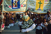 """Juchitàn, Velas (traditional celebrations) of Ixtepec.  """"Regada de Frutas"""", a procession along village's streets. The tehuanas are the archetype of an ancient and legendary Mexico, told in the murales of Diego Rivera and impersonated also by Frida Kalho that often wore these traditional dresses. But these showy dresses, and the rich golden ornaments that accompany them, are above all an instrument of auto-representatiom for these active women which the control of the local markets confers an independent economic power that is reflected in the self confidence. Even in the development of the festivities, where the women often dance a lot among them while the men remain seated watching."""