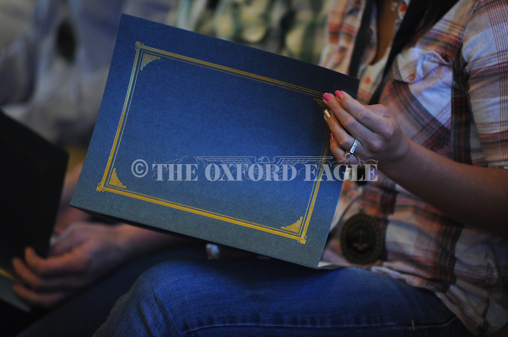 A Drug Court graduate looks over a certificate at Drug Court graduation at the Lafayette County Courthouse in Oxford, Miss. on Tuesday, February 10, 2015.