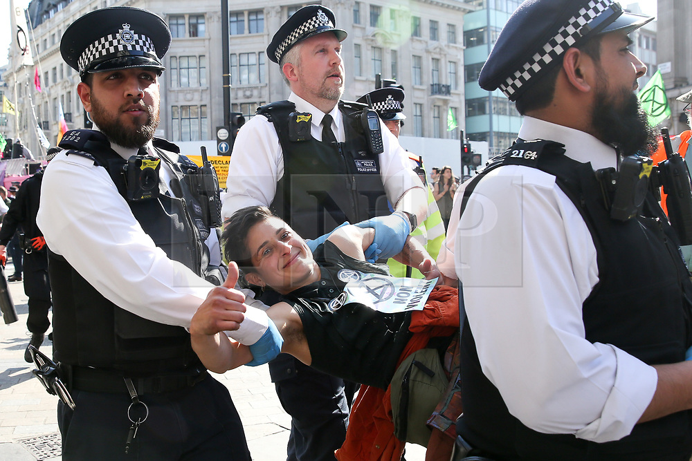 © Licensed to London News Pictures. 19/04/2019. London, UK. An environmental activist gives a thumbs up as he is detained by the police in Oxford Circus on the fifth day of the climate change protest by the Extinction Rebellion movement group. A large number of police presence around the pink boat as they un-bonding the activist who glued themselves and the police prepare to remove  from the site. According to the Met Police, over 700 activists have been detained over the past five days.  Photo credit: Dinendra Haria/LNP