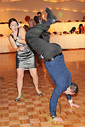 Wedding guests dancing on the ballroom floor at The Turning Stone Casino, and one guest is surprising his date by doing a handstand, Verona, NY