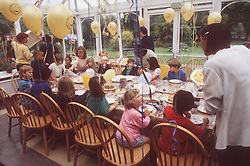 Multiracial group of children sitting around table at children's birthday party,