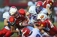 Marion's Tyler Gunderson (5) is hit by Decorah's Drew Schwartz (25) and Brett Johnson (2) during the game between the Decorah Vikings and the Marion Indians at Thomas Park in Marion on Friday, August 31, 2012.