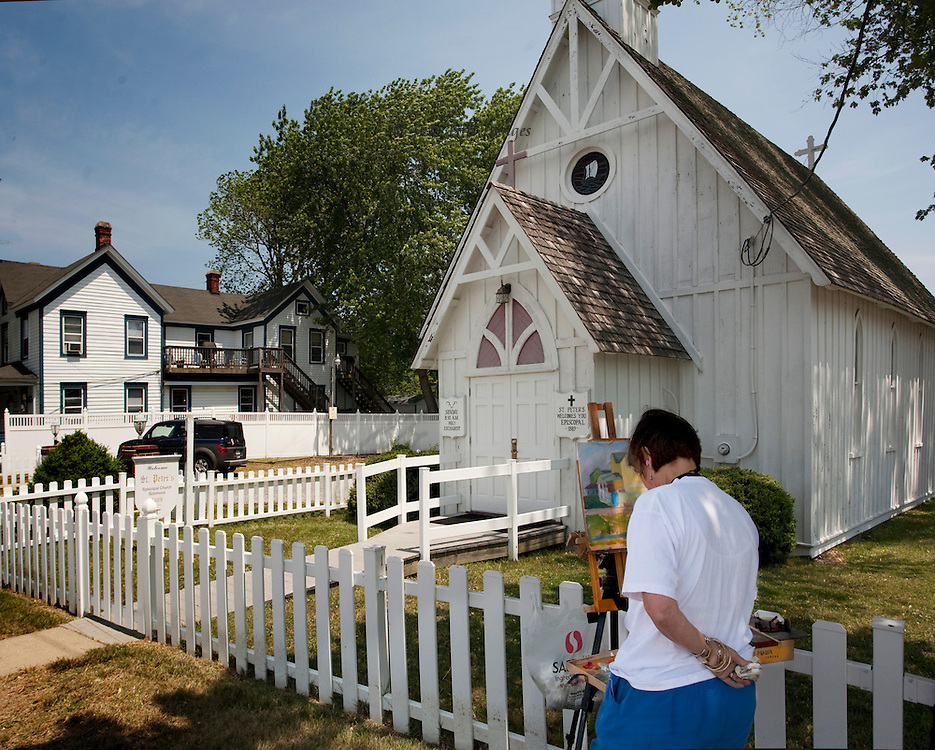 A member painter of the Mid-Atlantic Plein Air Painters' Association at work during a weekend event.  Behind the white picket fence is the very small wooden St. Peter's Episcopal Church of Solomon's Island, MD., built 1889.