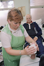 Nurse preparing patient's foot before applying a scotch cast diabetic boot for pressure relief in outpatients plaster room,