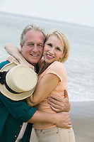 Middle-aged couple embracing on beach and looking at camera
